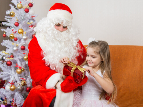 Girl opens a present with Santa